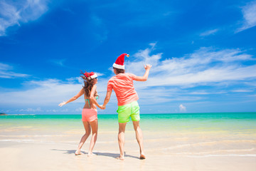 young couple in santa hats having fun at tropical beach. new