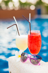 two glasses of cocktails and sunglasses by pool. party