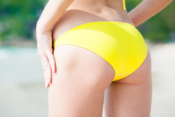back view of woman in yellow bikini