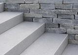 Moderne Natursteintreppe und Natursteinmauer in grau