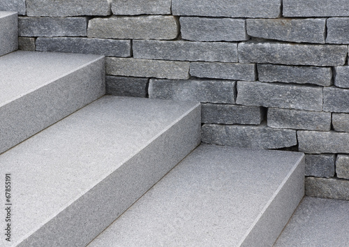 Fotobehang Trappen Moderne Natursteintreppe und Natursteinmauer in grau