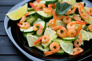 Shrimps, cucumbers and lime salad on a black glass plate