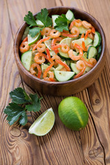 Wooden bowl with shrimps, cucumber and lime salad, studio shot
