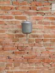 Old metal water dispenser basin on a brick wall.