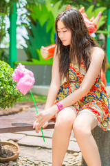 Cute Thai girl is sitting while holding pink candyfloss