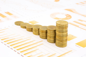 raising stacks of golden coins on business graph background
