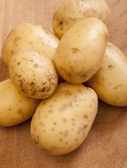 Potatoes on wooden background close up