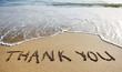 Leinwanddruck Bild - thank you word drawn on the beach sand