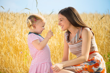 Happy young mother with daughter playing field
