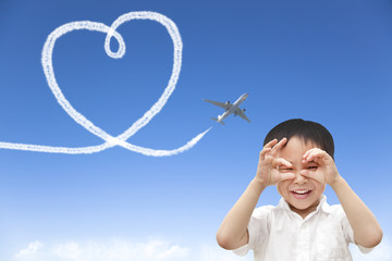 happy boy watching airplane flying and drawing a heart of cloud