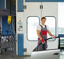 Cheerful serviceman with car door near paint booth