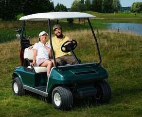 Happy couple driving golf cart