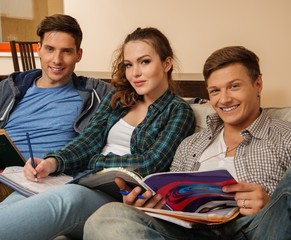 Three young students preparing for exams in apartment interior