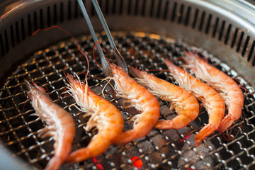 chef grilling shrimps on flame with tongs