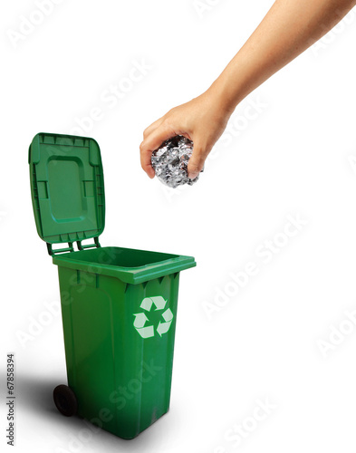 Hand throwing paper recycle into the green trash