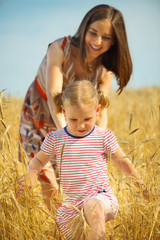 Young mother with little daughter at wheat field