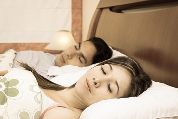 attractive couple lying in bed sleeping