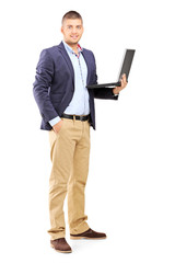 Full length portrait of a man holding a laptop