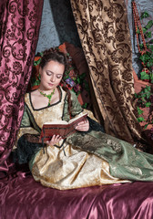 Beautiful woman in medieval dress reading book
