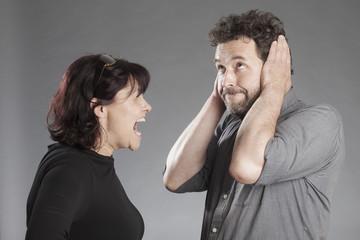 Mann hält sich Ohren zu, Frau schreit