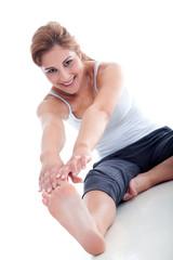 Junge sportliche Frau macht Gymnastik und lächelt
