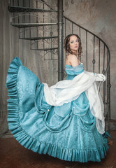 Beautiful woman in fluttering medieval dress on the stairway
