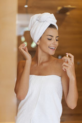 Beauty woman wrapped in towel applying perfume
