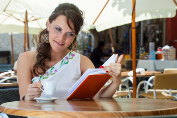 Young brunette woman is drinking coffee in a cafe