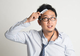 Asian businessman combing hair