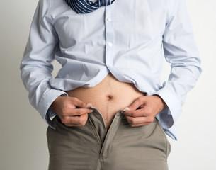 Man trying to fasten pants
