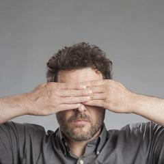 Mann hält sich die Augen zu, quadratisch