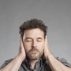 Mann hält sich die Ohren zu, quadratisch
