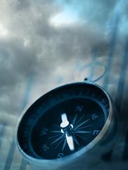 Compass on dark cloudy sky