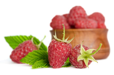 Sweet ripe raspberries in wooden plate isolated on white backgro
