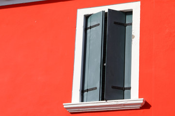 red wall of a House with the Green closed balcony