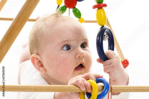 Leinwanddruck Bild Baby mit Greifspielzeug