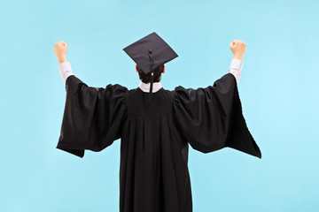 Overjoyed graduate student with raised fists