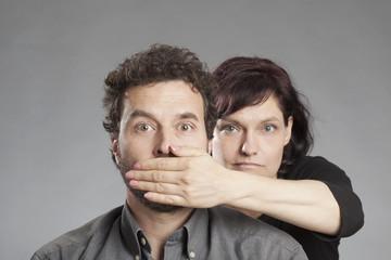 Frau hält Mann den Mund zu.