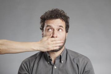 Hand hält Mann den Mund zu
