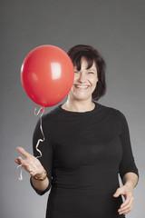 Frau mit rotem Ballon lachend