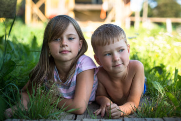 Little boy and little girl lying near a country house.