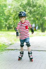 boy on rollers in the summer Park