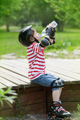 Boy on roller skates drinks water from bottle