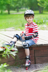 The child on rollers with a bottle of water rests