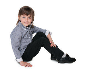 Fashion little boy sitting on the floor