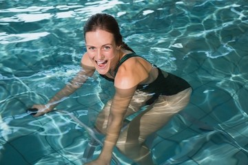 Fit happy brunette using underwater exercise bike