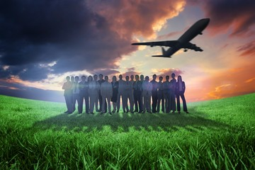 Composite image of business people standing up with airplane