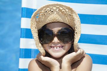 Niña con sombrero de paja y gafas de sol junto a piscina