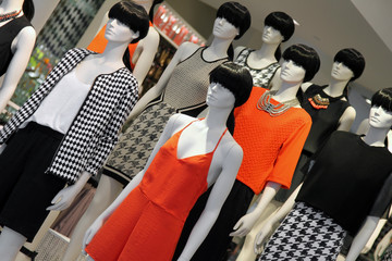 many fashion mannequins in the shop window