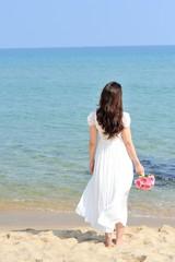 白いワンピースを着てピンクの花束を持って海に向かって立っている女性